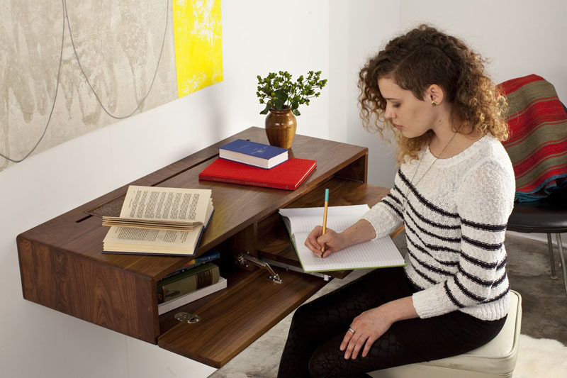 The front of this floating wall mounted desk flips down to reveal storage and a pull out desk.