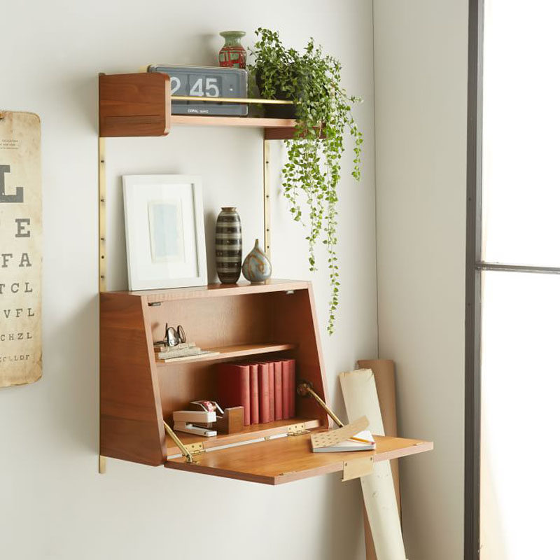 16 Wall Desk Ideas That Are Great For Small Spaces // The door of this shelving unit opens up to become the perfect writing surface that can also hide things when you close it up.