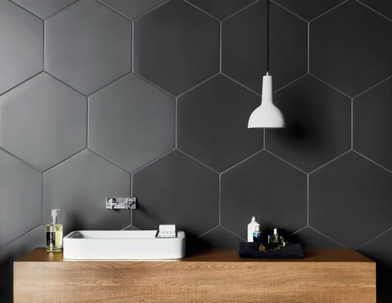 Bathroom Tile Ideas - Grey Hexagon Tiles // Large hexagonal charcoal tiles on the walls of this bathroom create a unique, modern look that compliments the wood countertop and contrasts the white sink and light fixture.