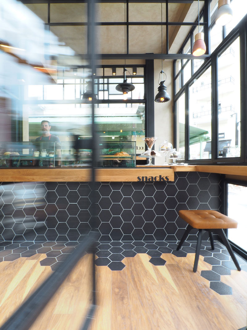 Hexagon tiles transition into wood flooring inside this cafe in inside the cafe black hexagon tiles wrap from the counter to the floor where they meet wood flooring dailygadgetfo Choice Image