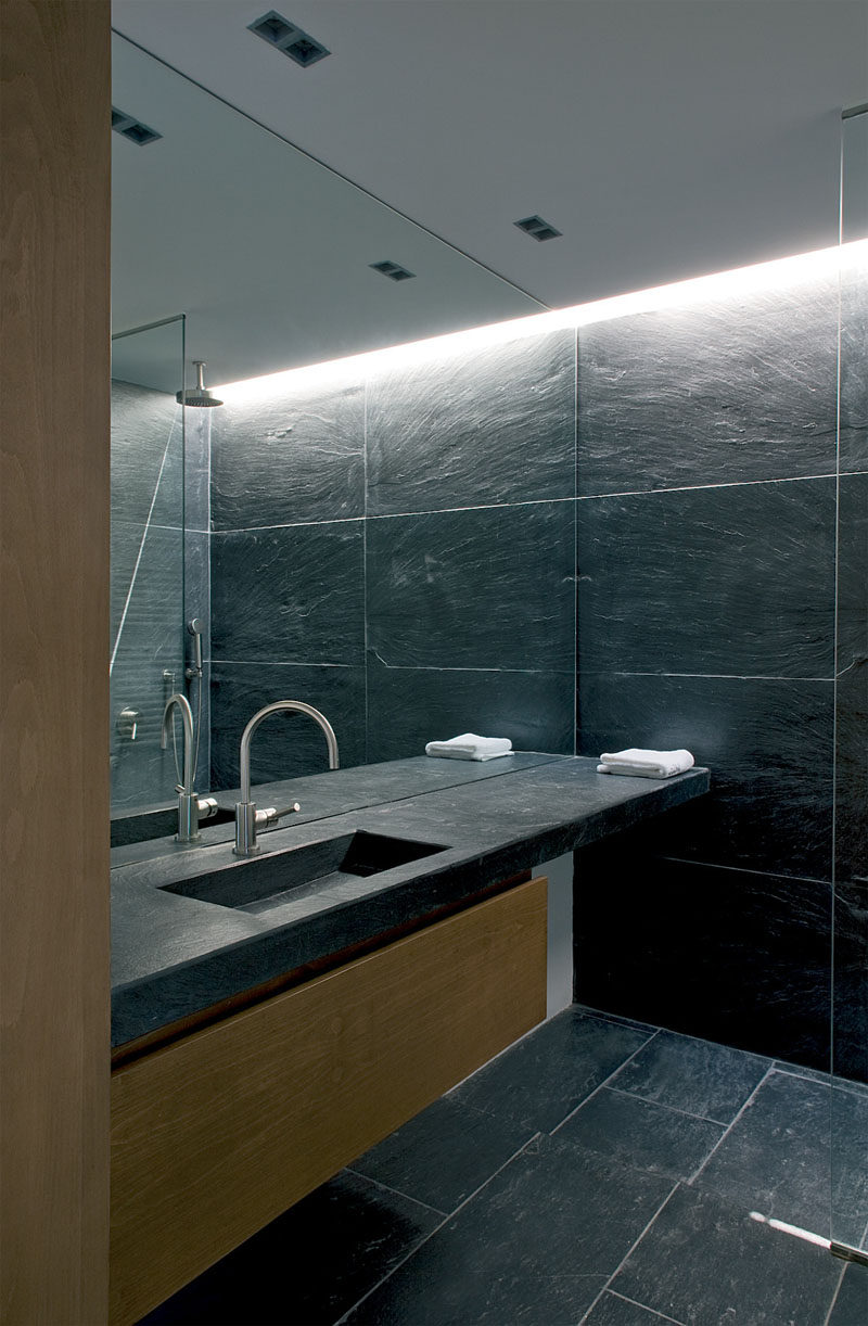 Bathroom Mirror Ideas - Fill The Wall // This full wall mirror starts at the level of the vanity and continues all the way up to the ceiling of this stone tile clad bathroom.