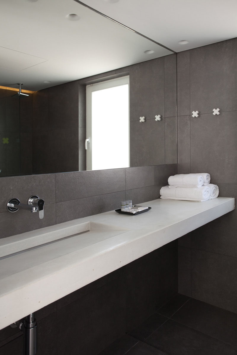 The Mirror Takes Up Most Of Wall Above Sink And Makes Gray Bathroom Feel Larger More Open