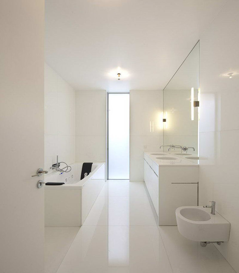 Luxury The mirror in this bathroom perfectly matches up with the double vanity beneath it and has the faucets ing out of it to create a seamless and continuous