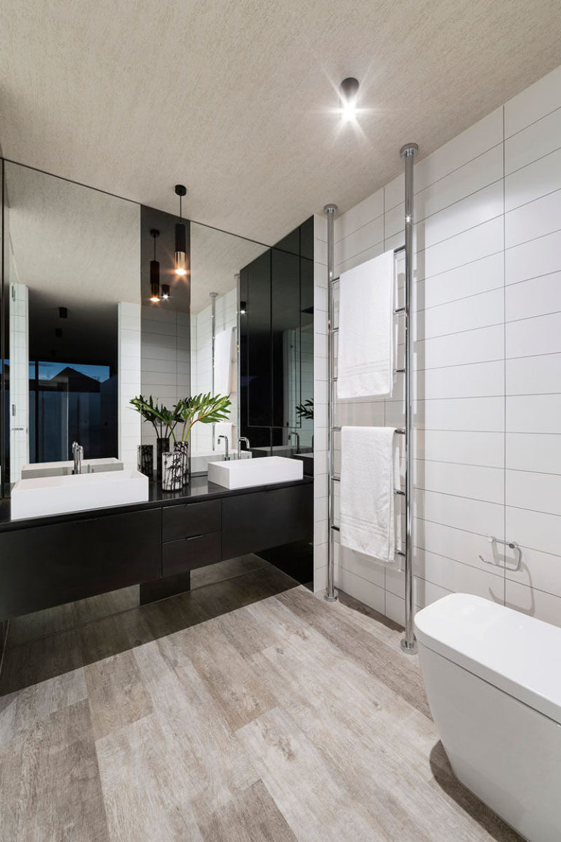 Bathroom Mirror Ideas - Fill The Wall // At first glance this looks like two separate mirrors but upon further inspection you'll notice that the strip down the middle is also part of the mirror, just a little darker to divide the vanity and give each person their space.