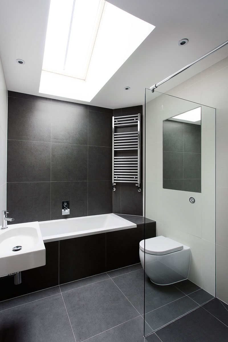 Bathroom Tile Ideas - Use Large Tiles On The Floor And Walls // The large black stone tiles in this bathroom help to create a simple black and white color scheme, and the light from the skylight makes the bathroom feel taller and more open.