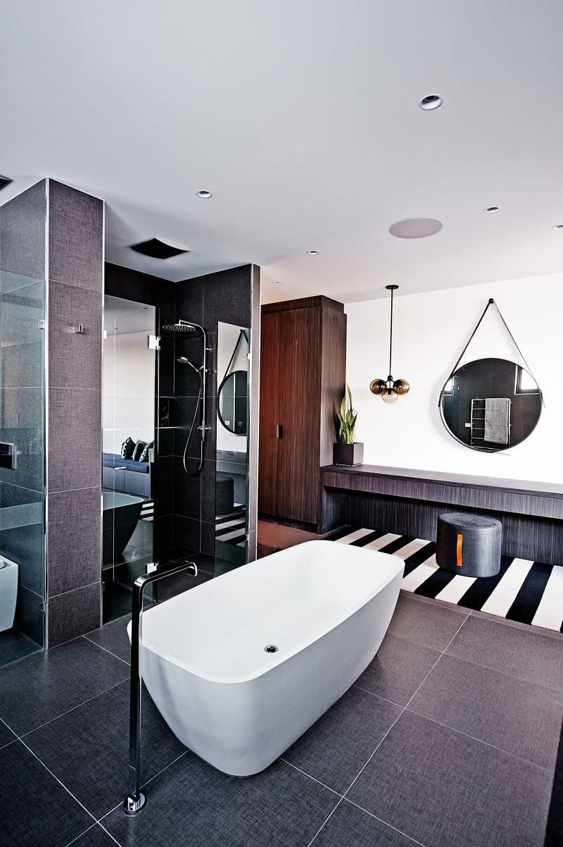 Bathroom Tile Ideas - Use Large Tiles On The Floor And Walls // The texture of the large dark tiles on both the floor and walls of this bathroom work well with the texture of the vanity and wardrobe, also found in the bathroom.