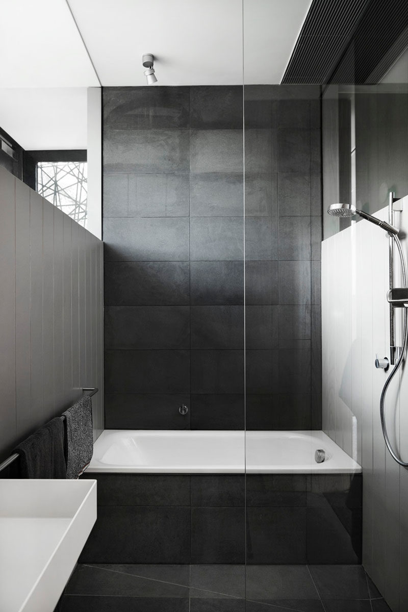 Bathroom tile idea use large tiles on the floor and walls 18 large dark tiles cover the floor bath surround and back wall of this bathroom creating a dark dramatic look but when paired with white walls it creates dailygadgetfo Gallery