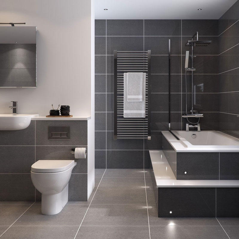 Bathroom Tile Ideas - Use Large Tiles On The Floor And Walls // Large dark grey tiles surrounded by white grout and white appliances makes this bathroom look clean, sleek, and relaxing.