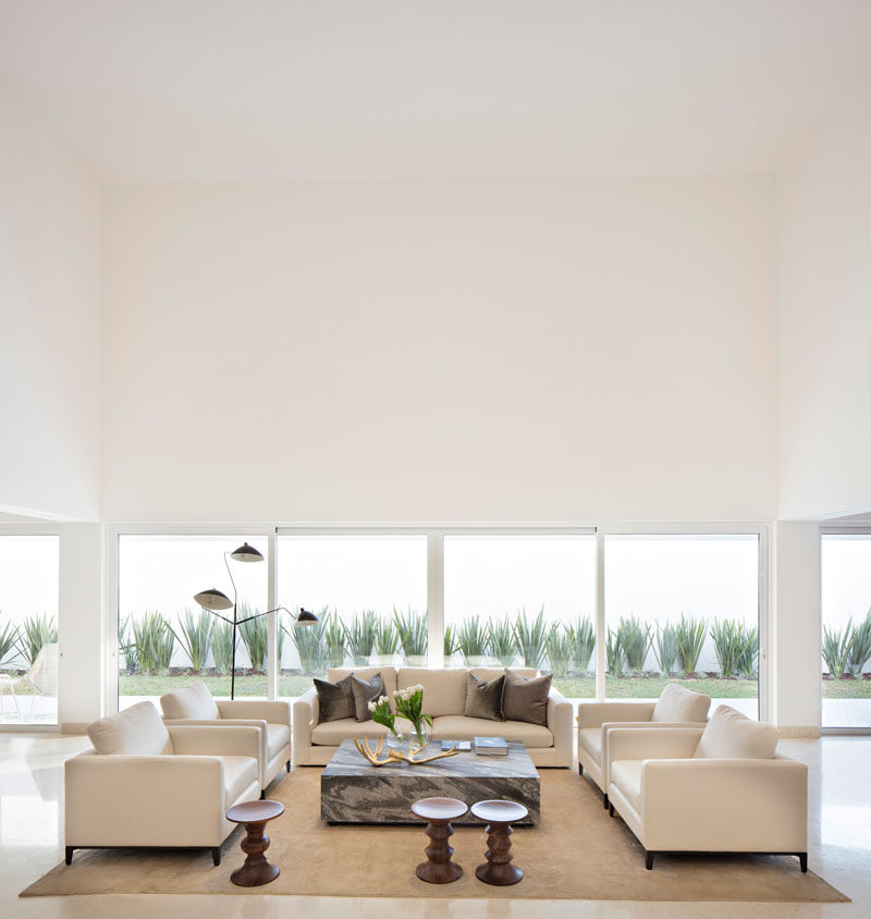 This sitting area has a double height ceiling that becomes the center of the home, and has views of the landscaped backyard.