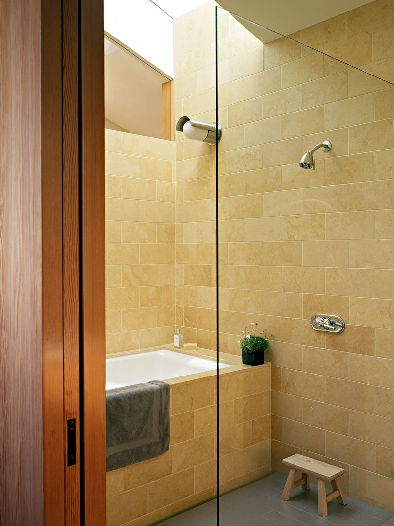 In this bathroom, light colored stone and a skylight keep the space bright and welcoming.
