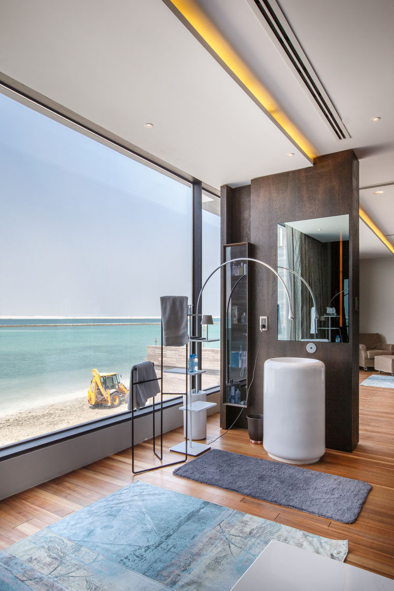 This master bathroom makes the most of the views through the large windows, and hidden lighting runs the length of the ceiling. #Bathroom #HiddenLighting