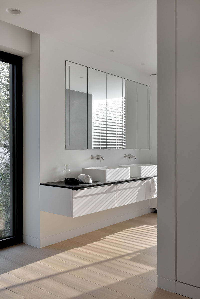 In this bathroom, large mirrors sit above the dual sink vanity and wooden floors help the space feel warm.