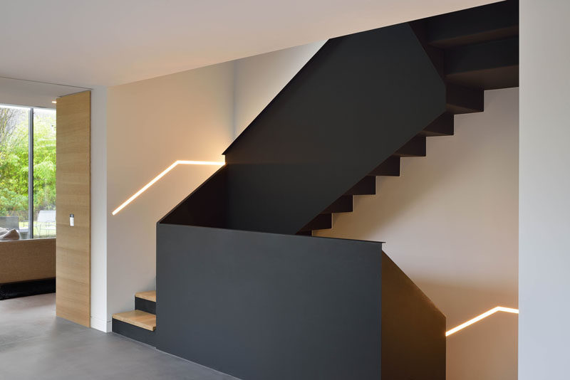 These black and wood modern stairs connect the various floors of this renovated home.