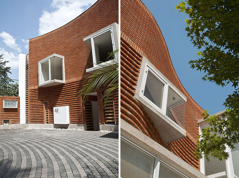 14 Modern Houses Made Of Brick // The bricks on this house have been arranged in a curved wave-like design to designate the private areas of the home. They also contrast the modern glass look of the more public areas on the first floor.
