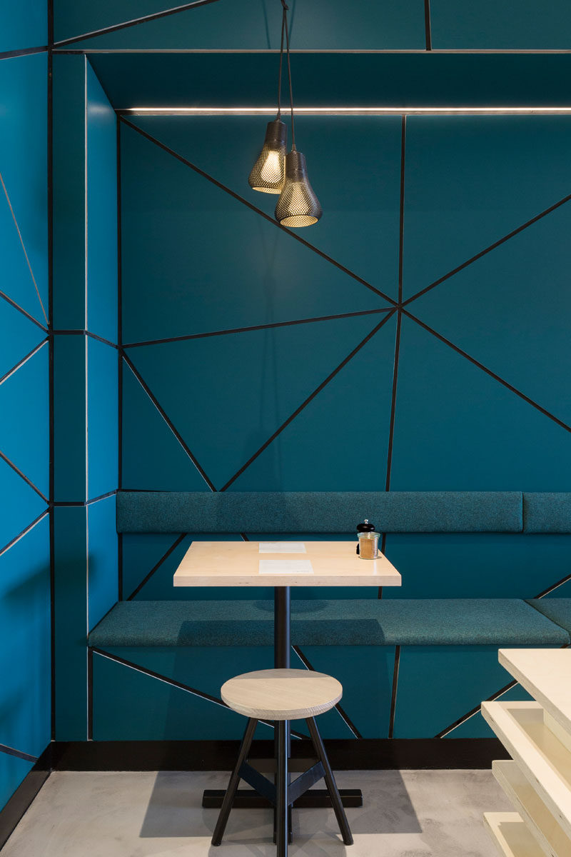 In this modern cafe, teal blue walls with a tessellated pattern have been paired with concrete flooring and light wood furniture.
