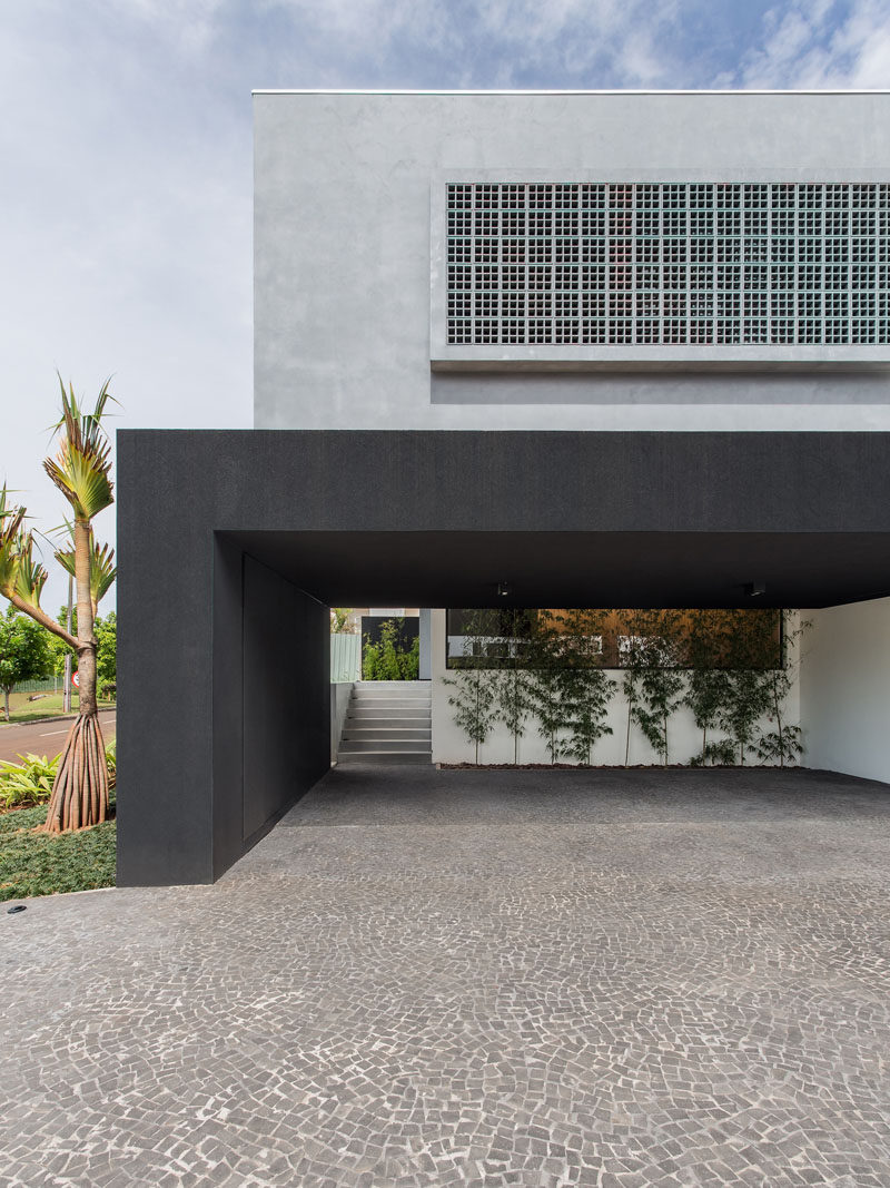 Located at the side of this house is a covered carport that's large enough to accommodate three cars, and also provides access to the home via a set of stairs.