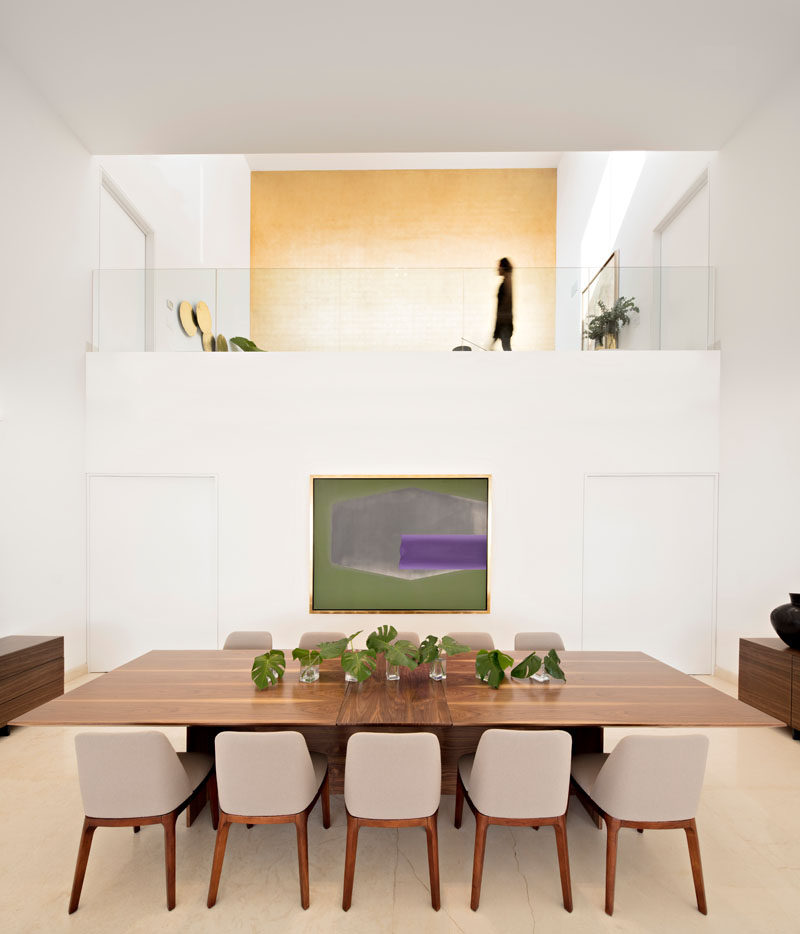 This dining room has a double height ceiling and views of a large gold wall that's located upstairs.