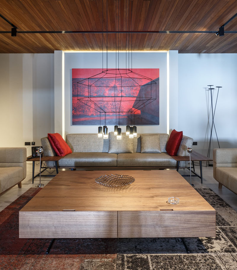 This formal lounge room has a minimal line chandelier, with bold red artwork and cushions adding a touch of color. #LoungeRoom #LivingRoom