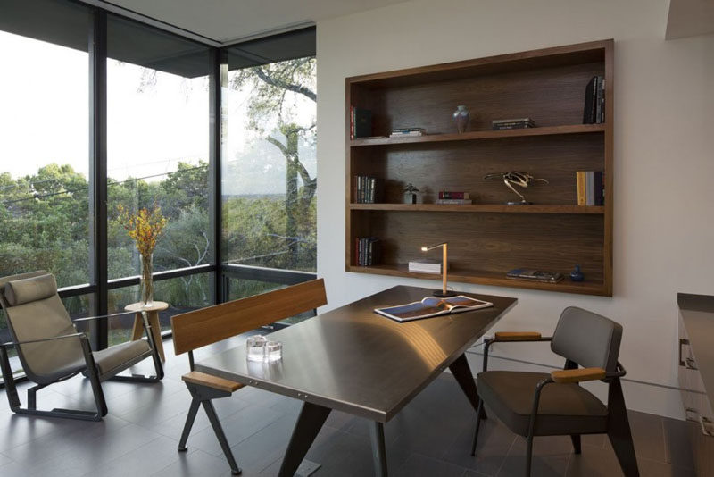 This home office has with large windows and built-in wooden shelving.
