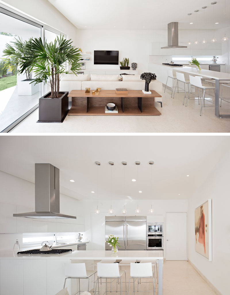 In this modern house, all of the public spaces are located on the ground floor of the home. A casual living room is located next to the kitchen that has a built-in dining table.