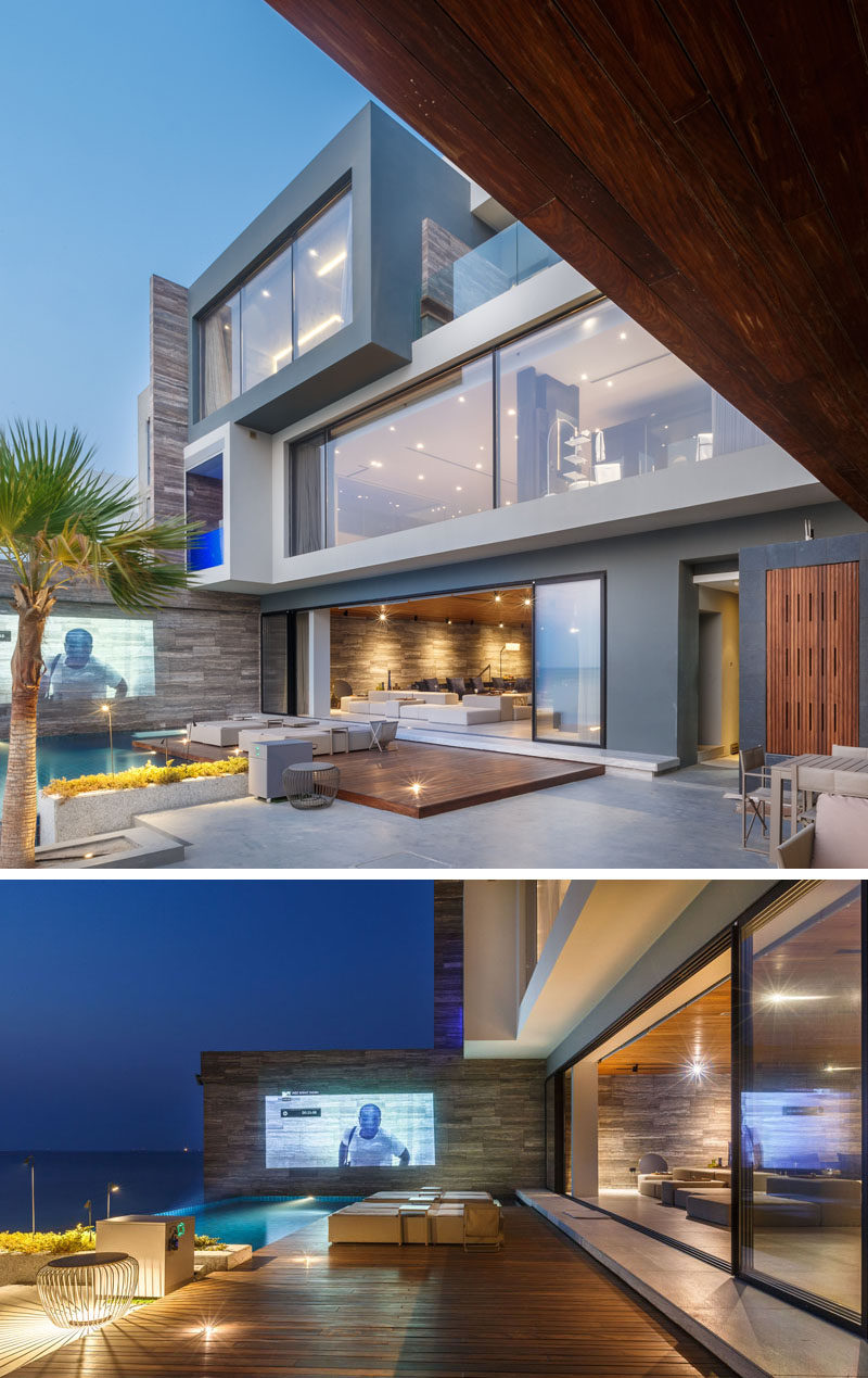 At night, movies can be projected onto the wall for outdoor entertaining at this house. #OutdoorSpace #OutdoorCinema
