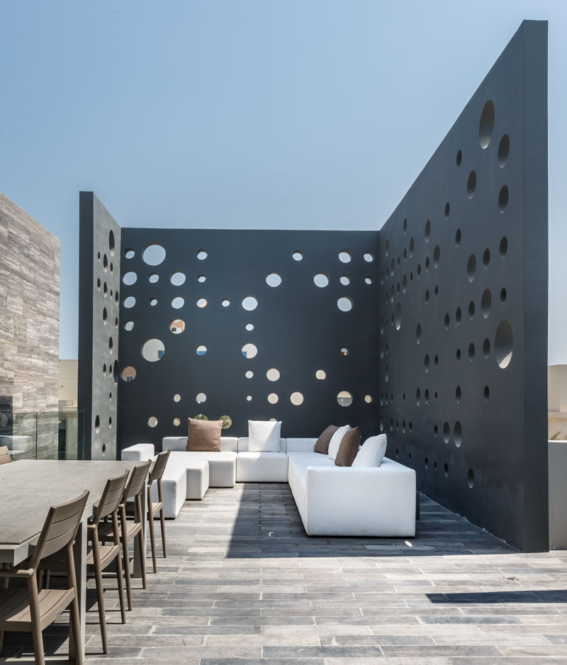 This home has a rooftop deck with lounge and outdoor dining area that's surrounded by perforated walls for privacy. #RooftopDeck #Screen #OutdoorScreen #Landscaping #LandscapeDesign