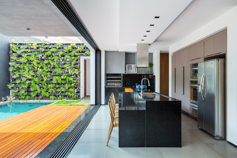 This gourmet kitchen, that opens to the backyard, has a central black island with a lower section that is the perfect height for a group of dining chairs.