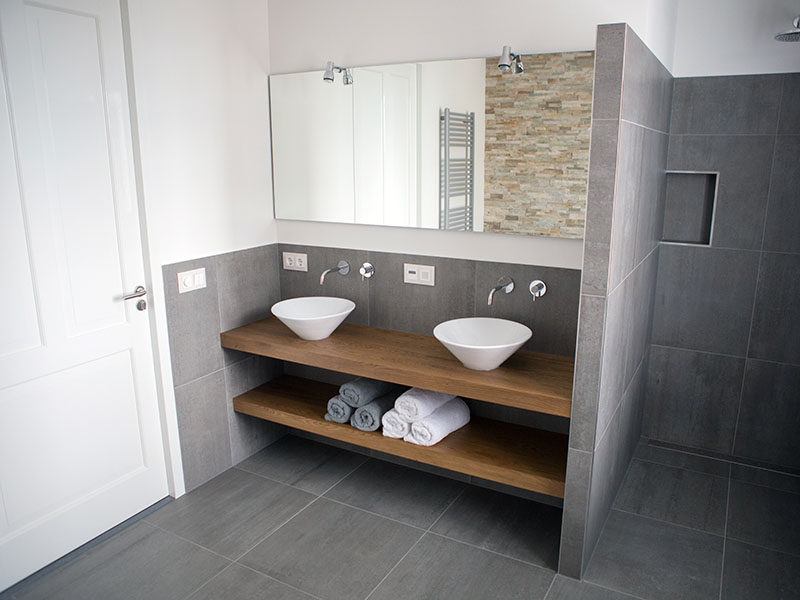 This Bathroom Predominantly Covered In Stone Tiles But Is Warmed Up With The Wood Counter And Shelf That Give It A Modern Inviting Look