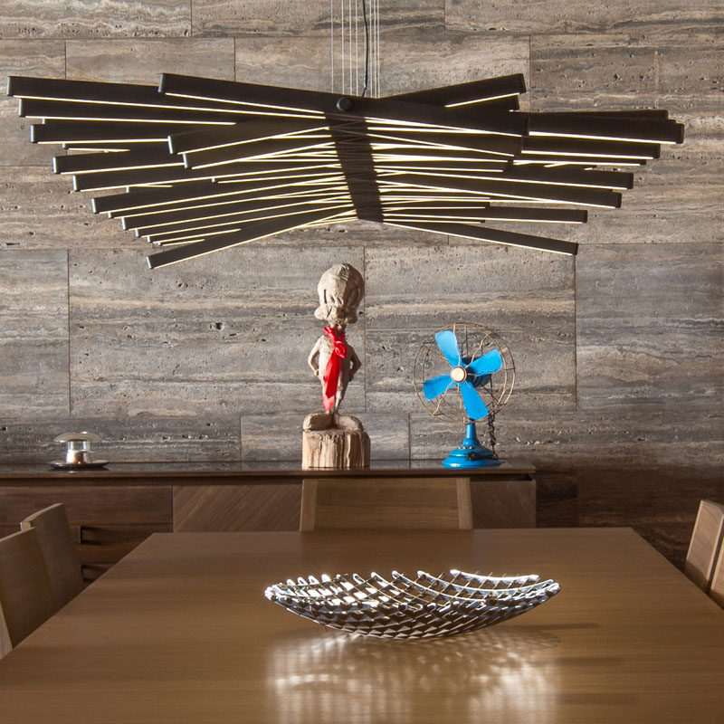 A sculptural light hangs directly above this dining table, while a wall of silver grey travertine runs the length of the home. #Lighting #DiningRoom