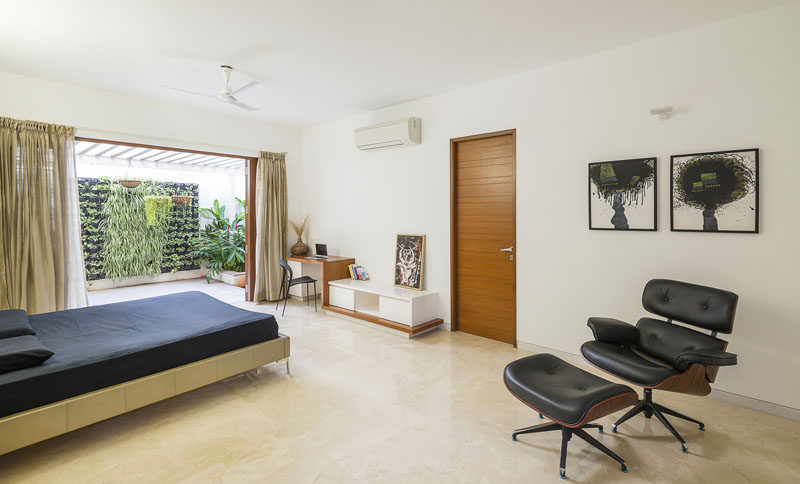This spacious bedroom with built-in desk features a private balcony with a small green wall.