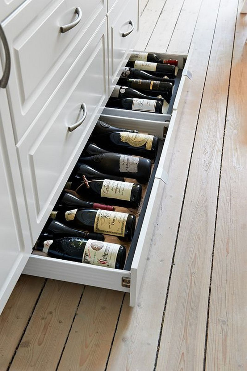 If you don't have the space or enough wine to justify a large wine rack, a toe  kick drawer might be all you need. It keeps the wine out of the way ...