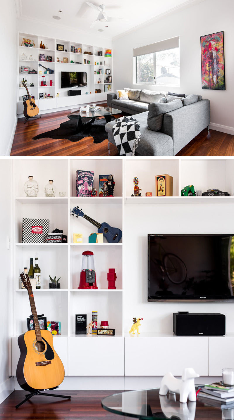8 TV Wall Design Ideas For Your Living Room // Square shelves surround the TV and bring in pops of color to the all white shelving unit.