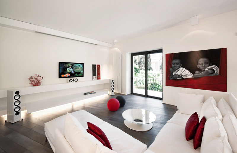 8 TV Wall Design Ideas For Your Living Room // The TV and the sound system in this white and red themed living room are surrounded by very little else and to make them the main focus in the room.