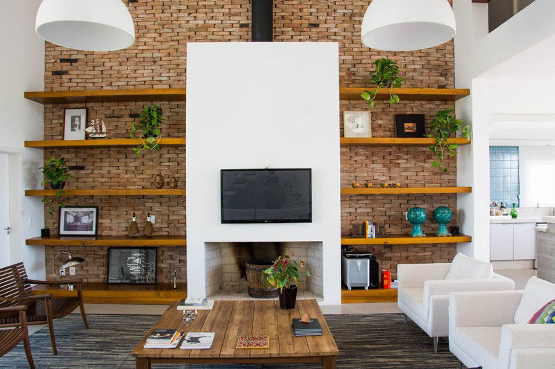 8 TV Wall Design Ideas For Your Living Room // A real fireplace sits beneath this TV that's also surrounded by storage to create a comfortable and practical living room.
