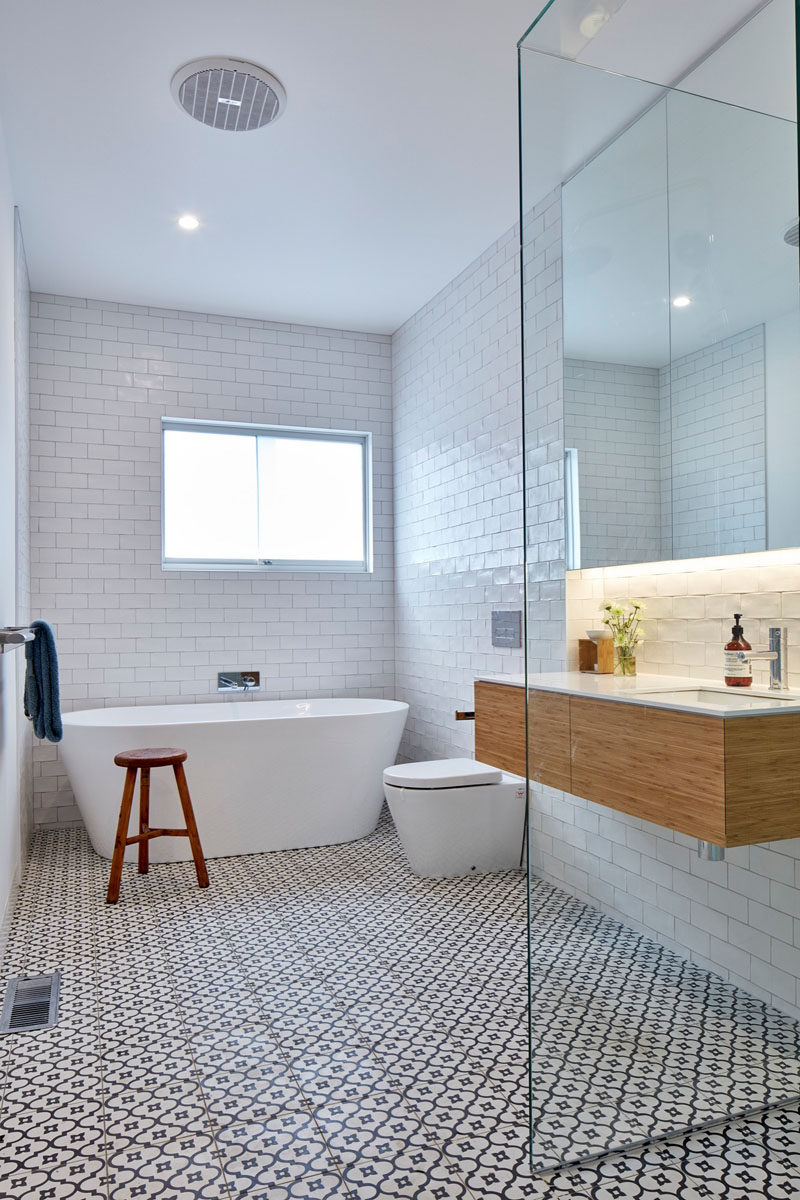 This bathroom features white subway tiles that cover the walls, and a decorative tile has been used on the floor.