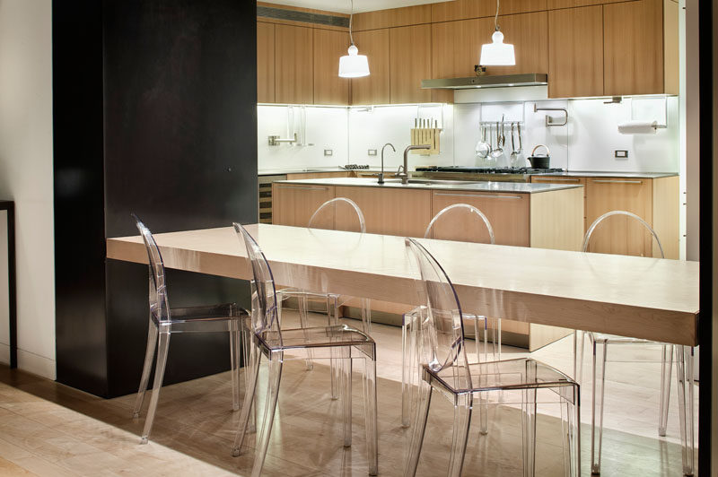 This modern home has a lower level with a full kitchen that features a built-in dining table between two steel supports.