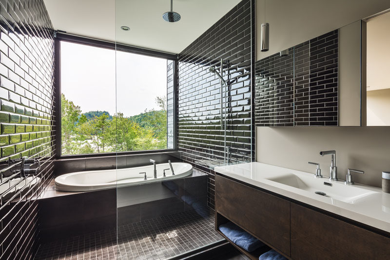 This ensuite bathroom has the shower and built-in bathtub partitioned off with a glass screen, while the black tile draws your eye to the tree-top view outside.