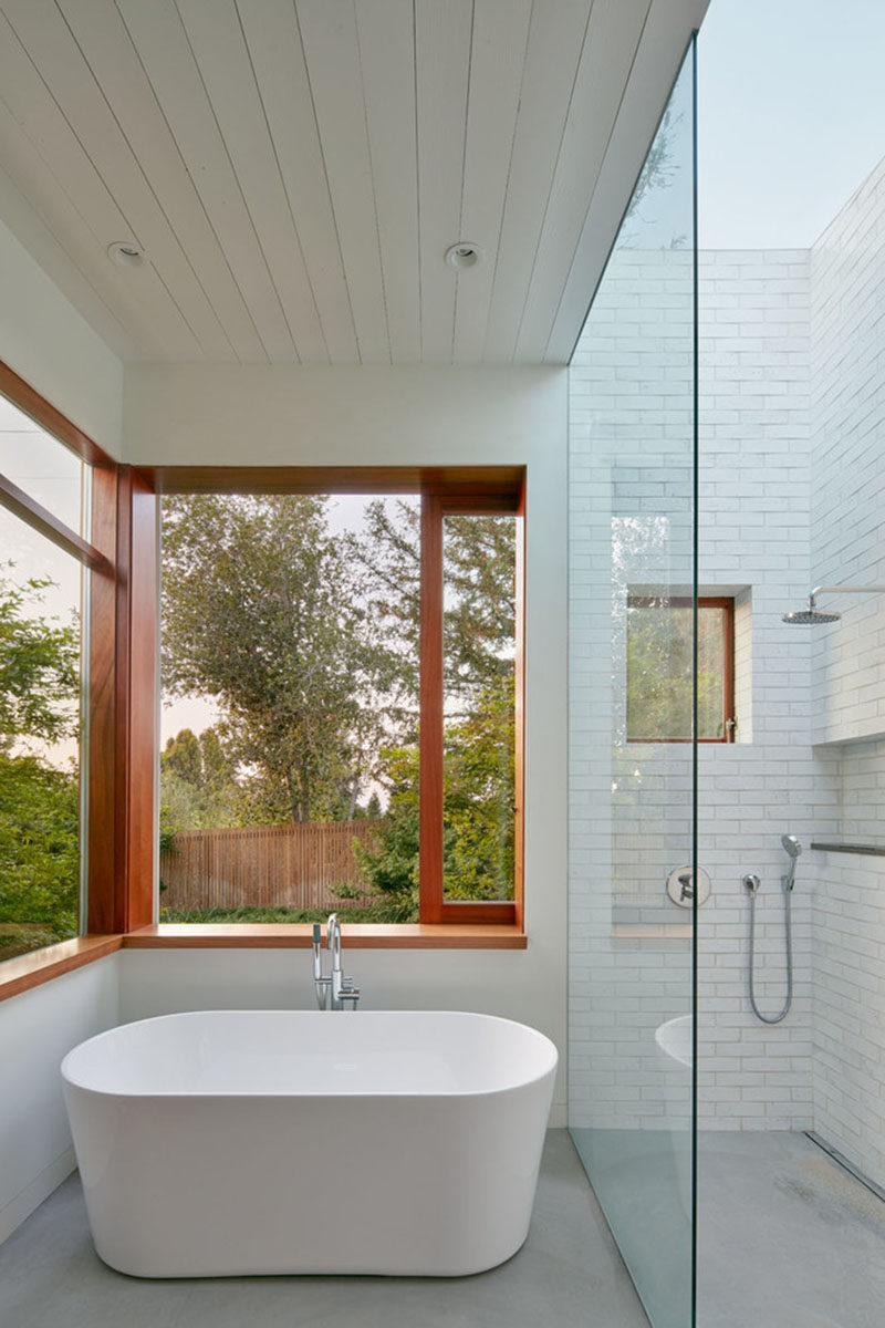 This master bathroom has a glass enclosed shower with skylight, and a deep soaker tub with views of the surrounding nature.