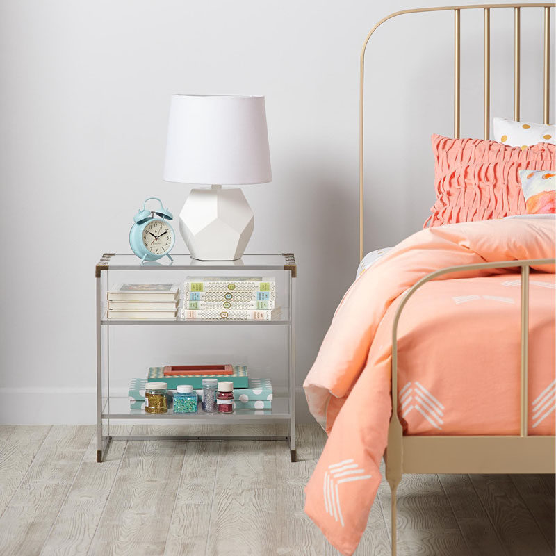 5 Ways To Use Acrylic Decor Throughout Your House // Bedroom - Brass details on the sides and bottom of this bedside table give it a more industrial look while still allowing it to keep the room feel airy.