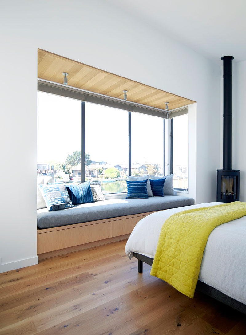 In this bedroom, a built-in upholstered window seat perfectly fits the length of the window and provides the perfect reading space.