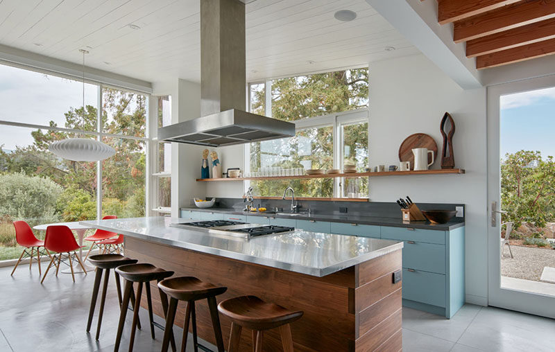 In this contemporary kitchen there's a large island with a walnut base and a stainless steel countertop that surrounds the cooktop. Against the wall, light blue cabinets add a pop of color and an open shelf lets the home owners display their favorite kitchen items.