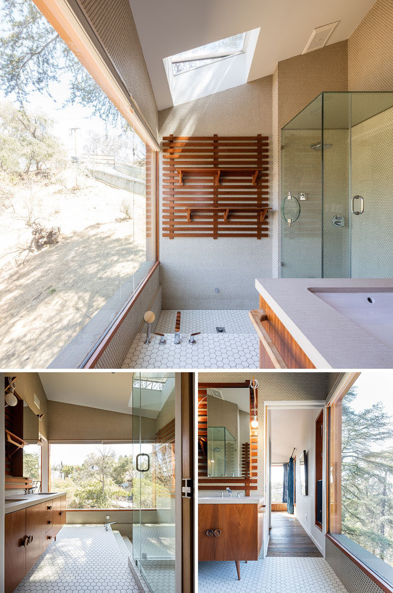 This contemporary bathroom has a skylight, a sunken bath, and views of the valley below.