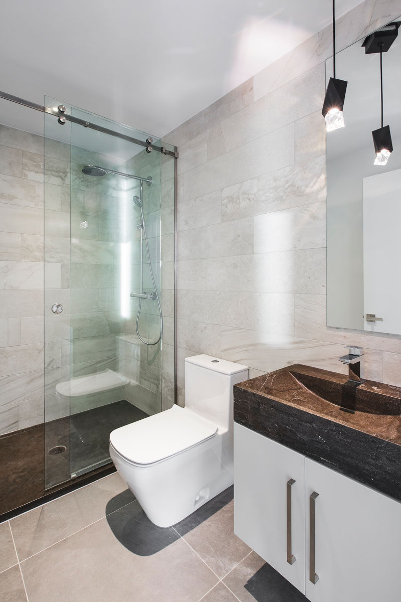 In this modern guest bathroom, the dark flooring in the shower matches the stone vanity.