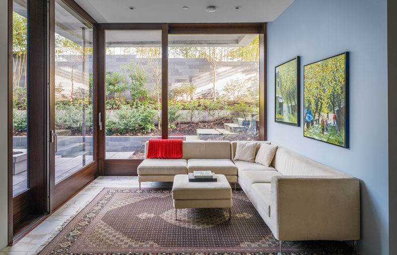 This corner living room has large sliding glass and wood doors that open up to an outdoor area.