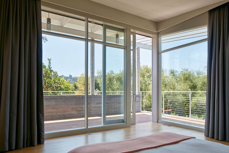 This master bedroom has large floor-to-ceiling windows, and sliding doors provide access to a covered porch.