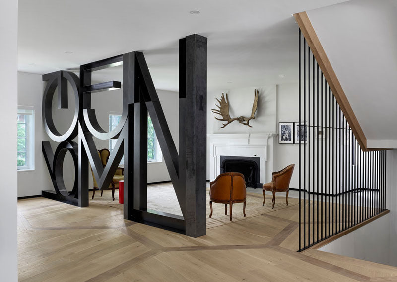 In this formal living room in a renovated heritage house, a word art installation by Commute Design takes the place of a wall. The home owners use this heritage part of the home to display their collection of vintage chairs.