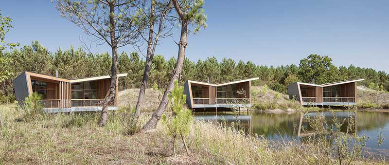 Patrick Arotcharen Architecte has designed a golf and surf eco-lodge in Saubion, France, named Les Echasses, where each of the private villas and restaurant have butterfly roofs.