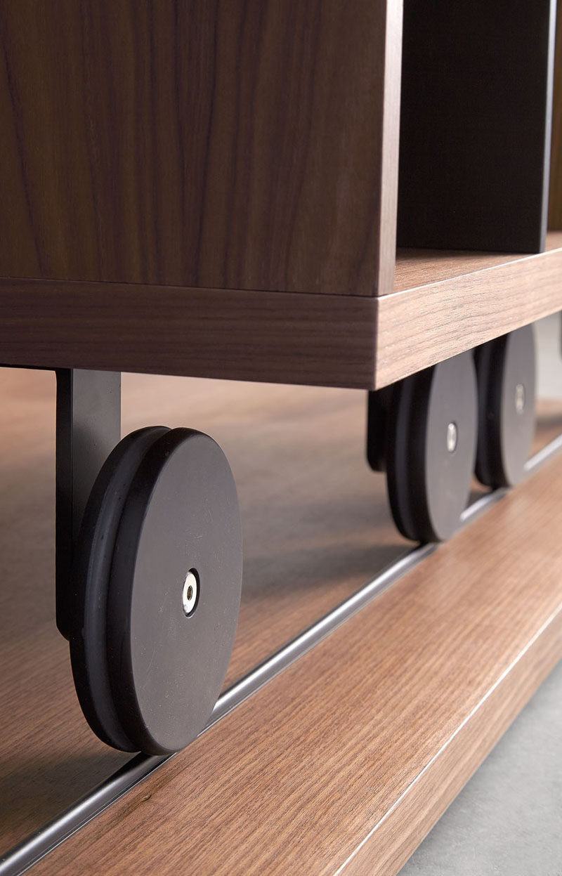 The wheels on the bottoms of this bookcase add an industrial touch to the modern piece of furniture.