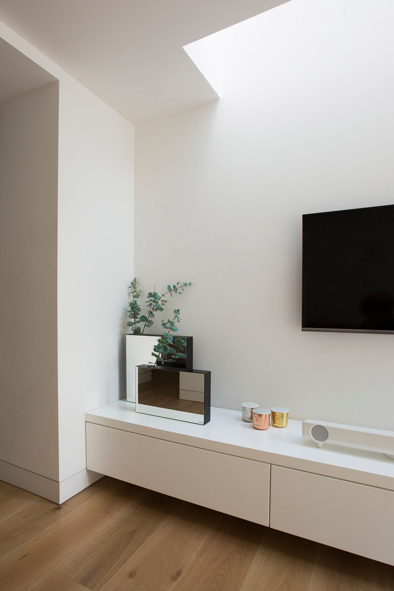 This built-in furniture includes cabinets to allow for convenient storage and doubles as a shelf that holds decor pieces and essential electronic components.