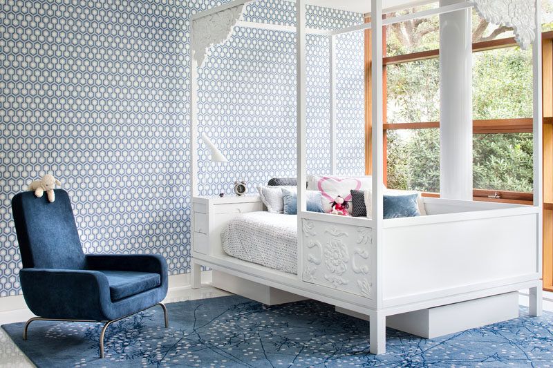 Playful patterned wallpaper covers the wall in this children's bedroom.